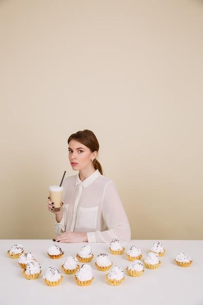 深刻な若い女性がコーヒーを保持しているカップケーキに近いポーズ 無料写真