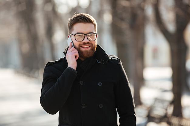 冬の屋外で携帯電話で話している幸せな若い男 無料写真