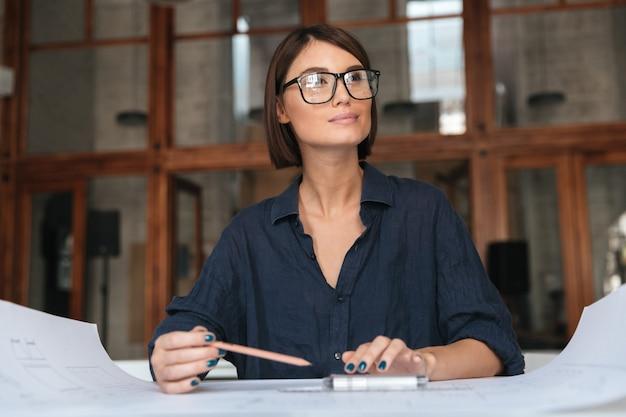テーブルに座って眼鏡で思いやりのある笑顔のビジネス女性 無料写真