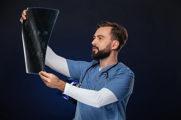Портрет концентрированный мужской доктор, одетый в форму Бесплатные Фотографии
