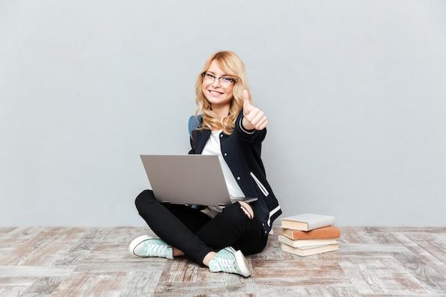 Счастливый студент молодой женщины используя портативный компьютер. Бесплатные Фотографии