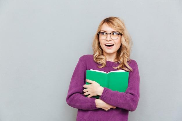本をよそ見を持つ女性 無料写真