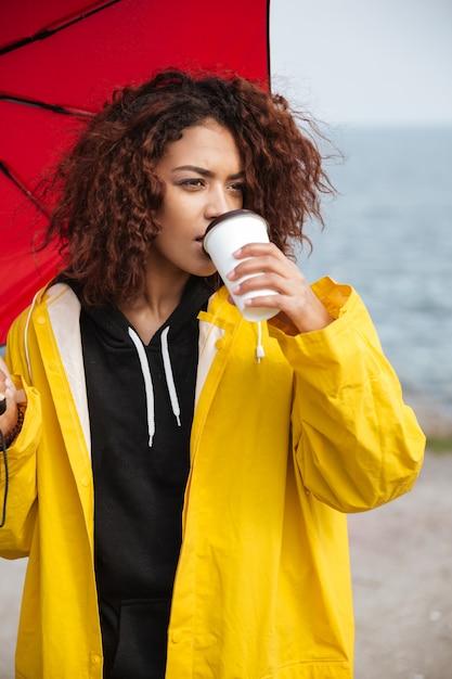 野外を歩いていると、コーヒーを飲みながらアフリカの巻き毛の若い女性を集中してください。 無料写真
