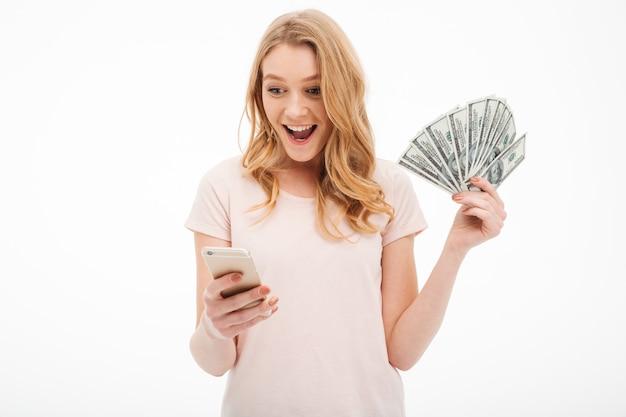 Возбужденных молодая леди, держа деньги с помощью мобильного телефона. Бесплатные Фотографии