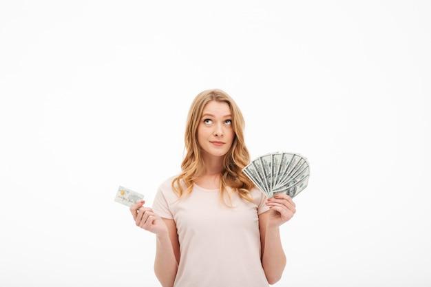 お金とクレジットカードを保持している若い女性を考えます。 無料写真
