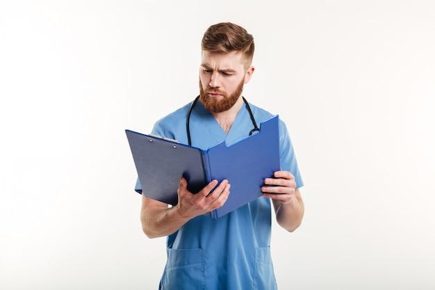 クリップボードを見て聴診器で物思いにふける医師や看護師 無料写真