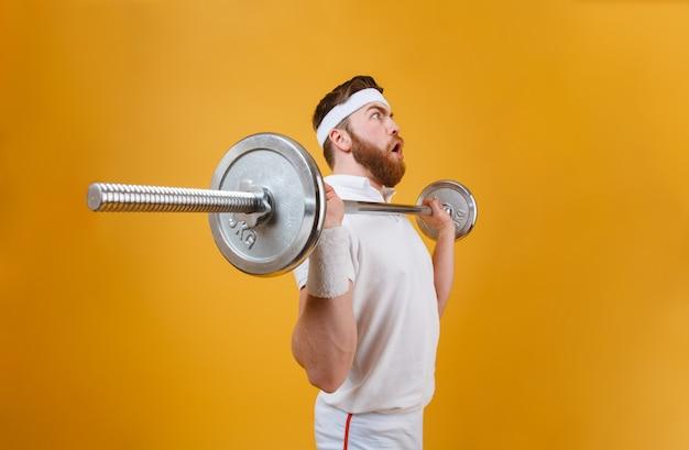 Сконцентрированный молодой спортсмен делает спортивные упражнения со штангой Бесплатные Фотографии