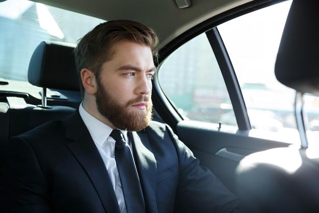 Человек в костюме сидит на заднем сиденье автомобиля Бесплатные Фотографии