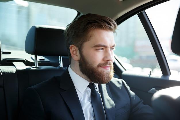 Молодой улыбающийся бизнесмен, сидя в машине Бесплатные Фотографии