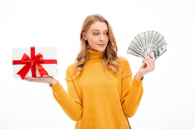 お金と驚きのギフトボックスを保持している若い女性。 無料写真