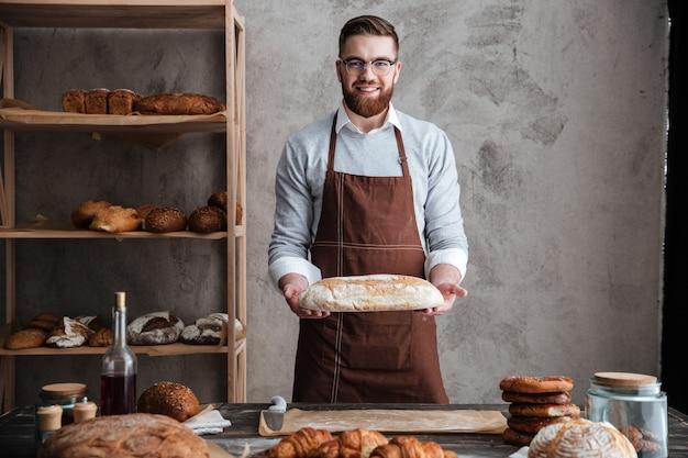 陽気な若い男のパン屋のパンを保持しているベーカリーに立っています。 無料写真
