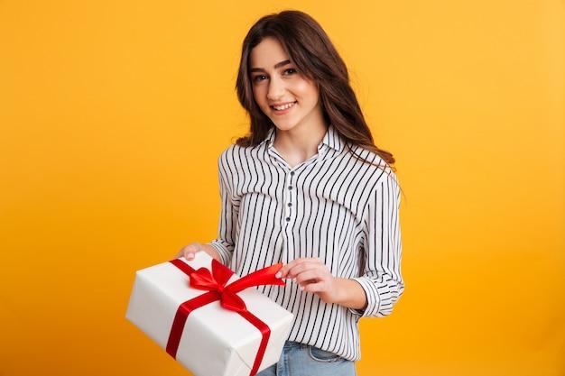 ギフト用の箱を開く笑顔の若い女の子の肖像画 無料写真