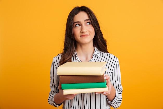 本を押しながら見上げるシャツで物思いに沈んだ笑顔の女性 無料写真