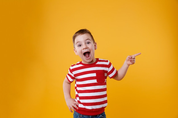 Удивлен счастливый мальчик, указывая пальцами Бесплатные Фотографии