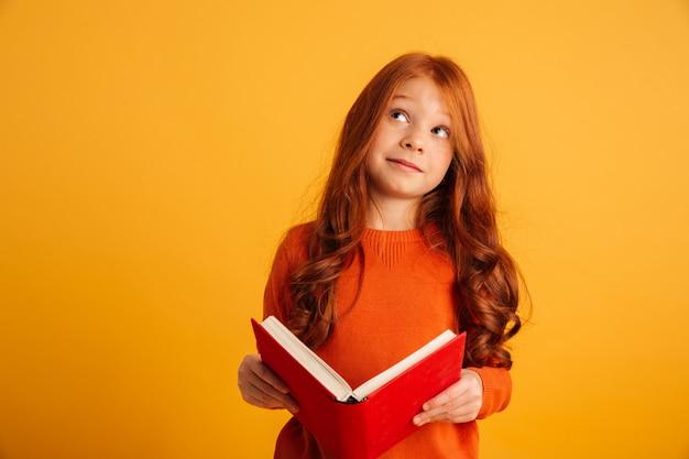 Думая маленькая рыжая девушка читает книгу Бесплатные Фотографии