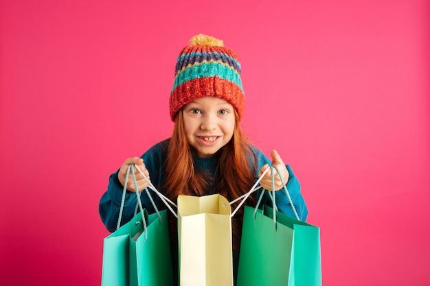 Счастливая красивая девушка держа хозяйственные сумки и смотря изолированную камеру Бесплатные Фотографии