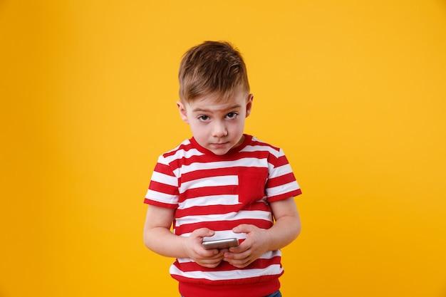 Грустный маленький мальчик держит мобильный телефон Бесплатные Фотографии