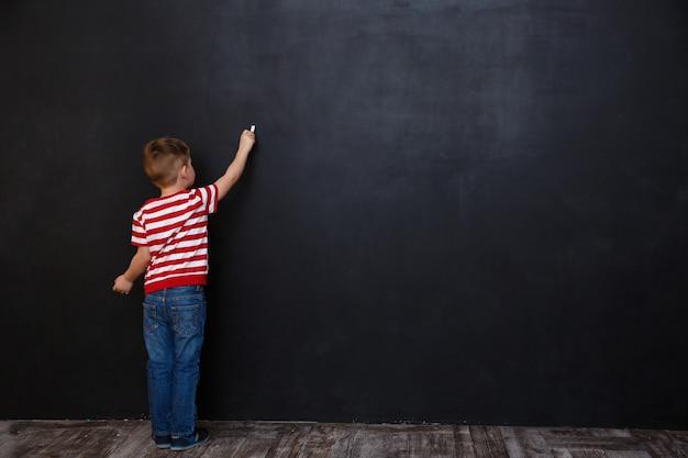 Вид сзади милый маленький мальчик, пишущий с мелом Бесплатные Фотографии