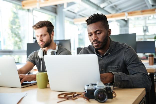 Серьезные молодые коллеги сидят в офисе коворкинг Бесплатные Фотографии