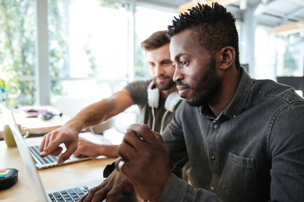 オフィスのコワーキングに座っている若い同僚を集中 無料写真