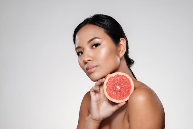Красивая спокойная женщина показывает кусок грейпфрута Бесплатные Фотографии