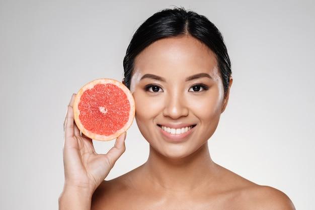 グレープフルーツのスライスを示す美しい女性 無料写真