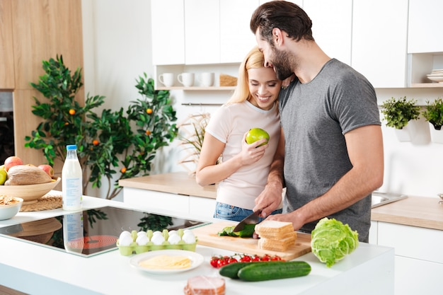 Улыбающиеся молодые влюбленные, стоя на кухне и приготовления пищи Бесплатные Фотографии
