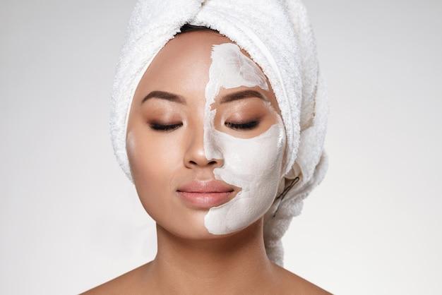 頭にタオルを持つ若い女性は彼女の顔にスクラブを置く 無料写真