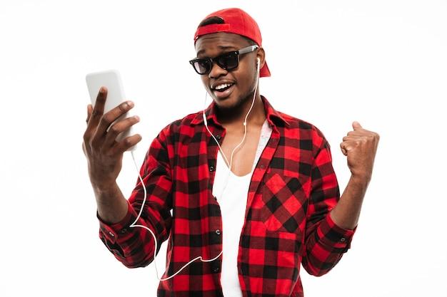 Счастливый человек стоял и слушал музыку с мобильного телефона Бесплатные Фотографии