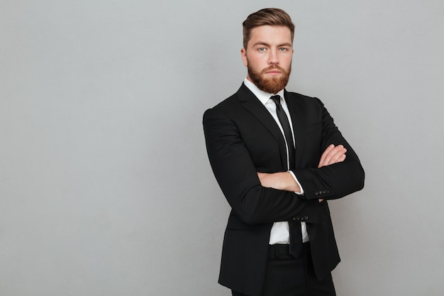 腕を組んで立っているスーツで自信を持って若いビジネスマン 無料写真