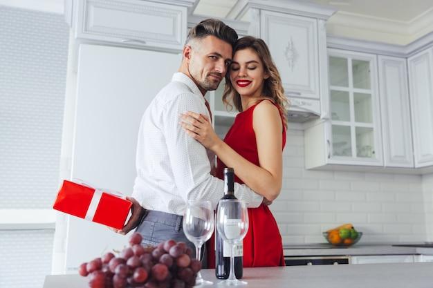 彼の素敵な女性、バレンタインデーのコンセプトのプレゼントを隠しながら自信を持って若者 無料写真