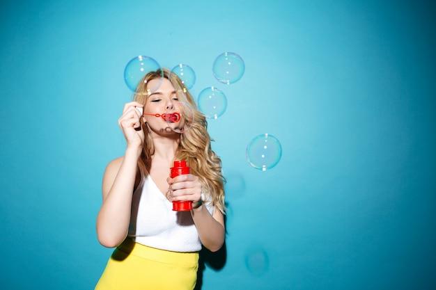 シャボン玉を吹く夏服でかなりブロンドの女性 無料写真