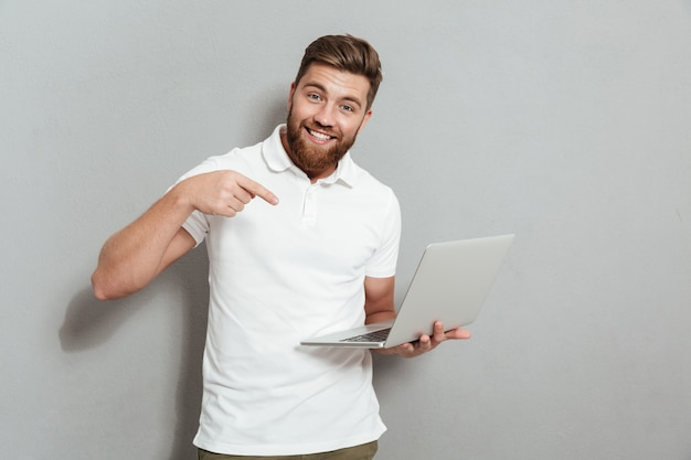 Счастливый бородатый мужчина держит ноутбук Бесплатные Фотографии