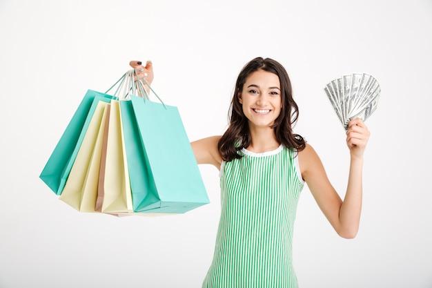 買い物袋を保持しているドレスで満足している少女の肖像画 無料写真