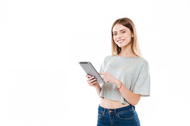 立っているとタブレットコンピューターに触れる笑顔の女の子の肖像画 無料写真