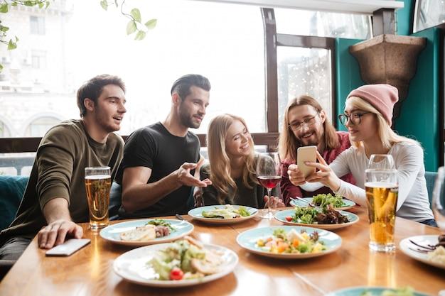 Веселые друзья сидят в кафе, разговаривают друг с другом. Бесплатные Фотографии