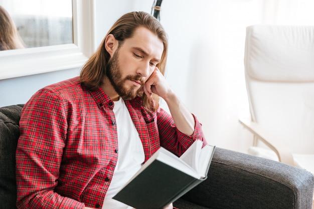 Серьезный бородатый молодой человек сидит и читает книгу дома Бесплатные Фотографии