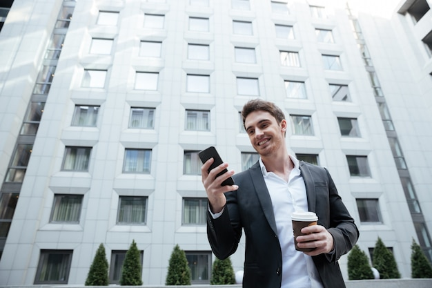 Улыбающийся бизнесмен с кофе с помощью смартфона в бизнес-центре Бесплатные Фотографии