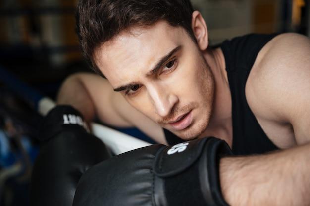 ボクシングのリングで若い強力なボクサーのトレーニング。 無料写真