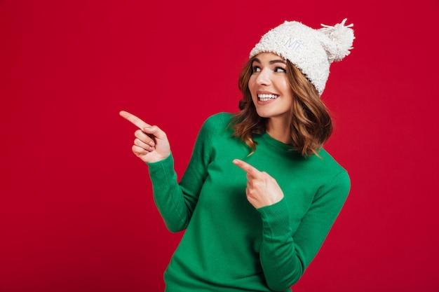 セーターと離れて指している面白い帽子で笑顔のブルネットの女性 無料写真
