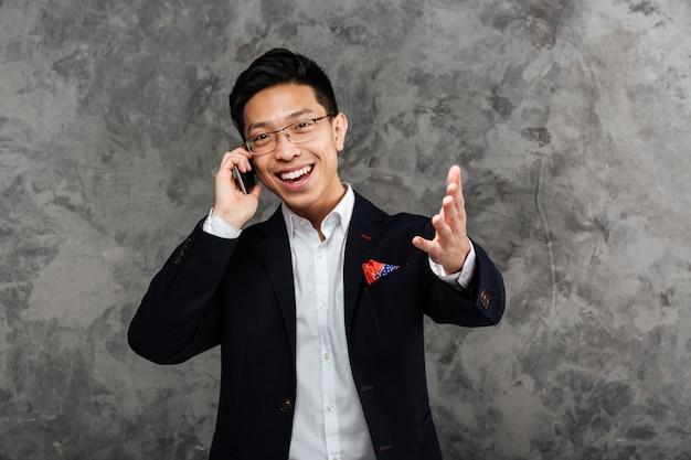 Портрет удовлетворенного молодого азиатского человека одел в костюме Premium Фотографии