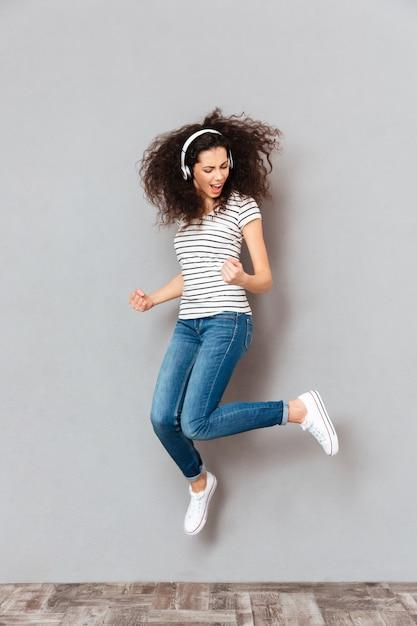 遊び心のある女性のダンスとイヤホンで音楽を聴きながら灰色の壁に髪を振ってパーティーのフルサイズビュー 無料写真