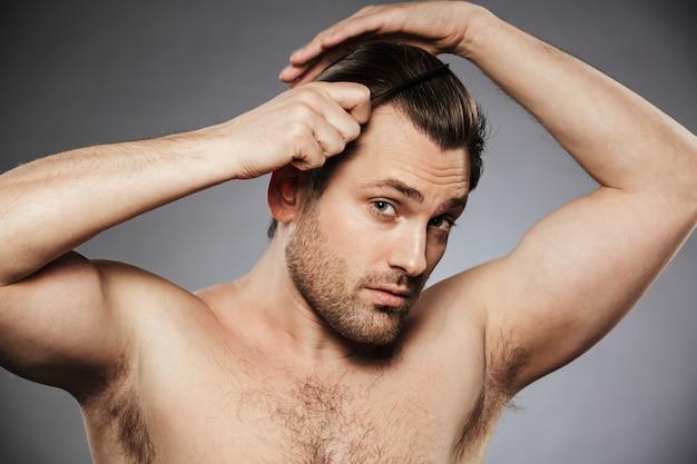Портрет обаятельного мужчины без рубашки, расчесывающего волосы Premium Фотографии