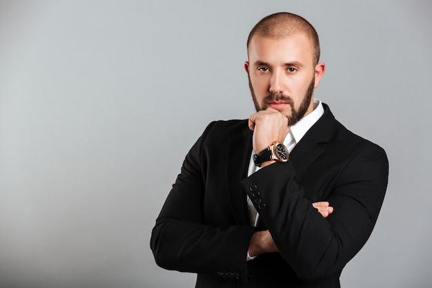 彼のあごに触れると灰色の壁に分離された意味のあるビューでポーズをとって黒のビジネススーツで集中して成人男性のイメージ Premium写真