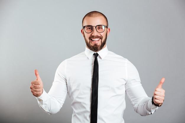 Изображение восторженного кавказского человека в белой рубашке и очках улыбается и показывает палец вверх, изолированных на серую стену Premium Фотографии