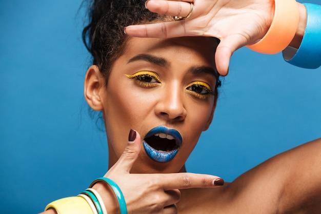 Портрет стильной очаровательной женщины с красочными макияж и вьющимися волосами в булочке, указывая на камеру с улыбкой, изолированных на синей стене Бесплатные Фотографии