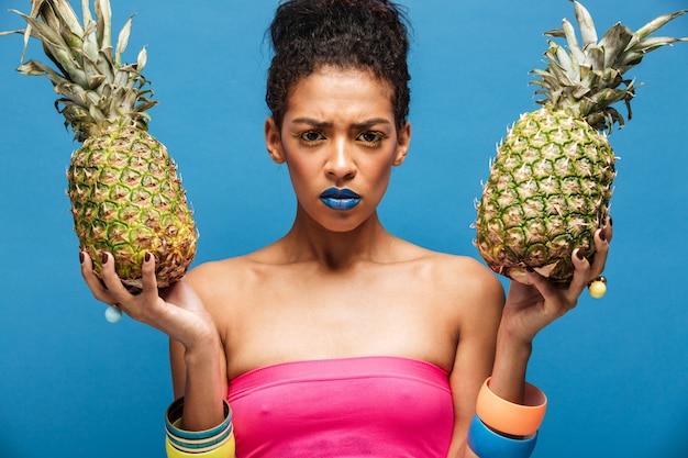 Портрет серьезной женщины мулата с хмурым лицом стильной внешности, расстроенным, держащим два спелых ананаса в обеих руках, изолированных по синей стене Бесплатные Фотографии
