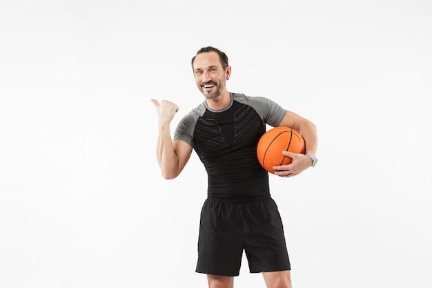 バスケットボールを保持している笑顔の成熟したスポーツマンの肖像画 Premium写真