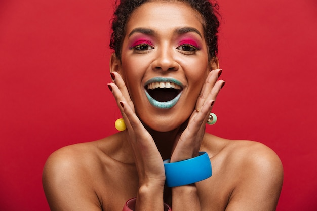 赤い壁の上の顔で手を繋いでいるカメラで叫んでトレンディな化粧品で多色幸せなアフリカ系アメリカ人女性 無料写真
