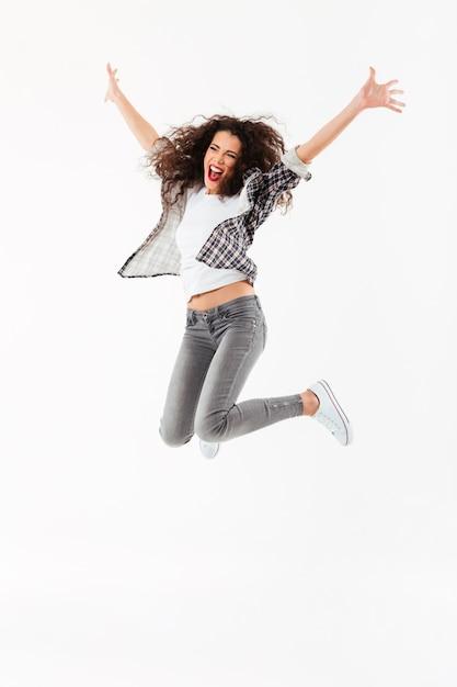 完全な長さの陽気な巻き毛の女性ジャンプと白い壁を越えてよそ見 無料写真
